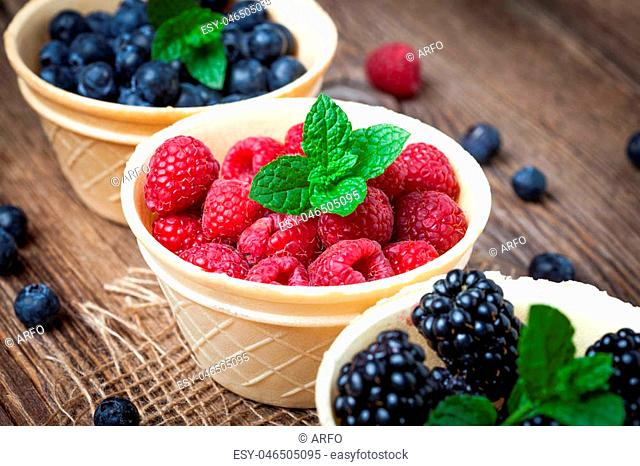 Blackberries, raspberries and blueberries in a waffle bowls on a wooden table. Selective focus