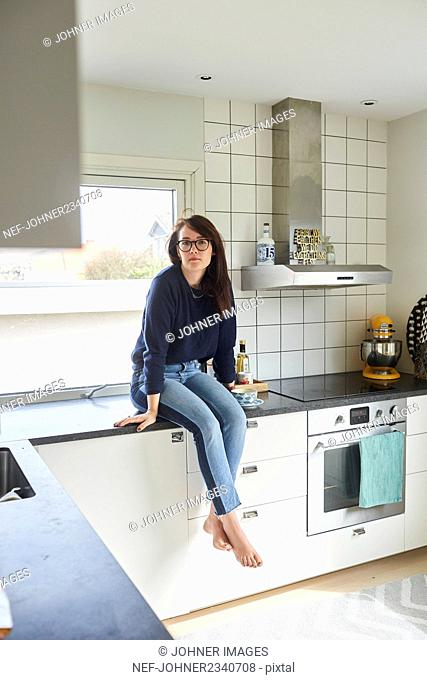 Young woman sitting on kitchen counter
