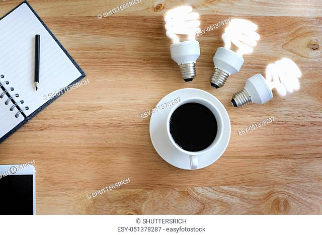Brainstormneed the power. Coffee Mug on a Wooden Tabletop is the best for creat new project. Black coffee on wood table. And lamp