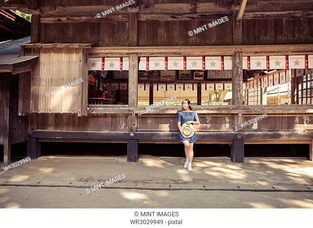 Young woman wearing blue dress and holding hat standing at Shinto Sakurai Shrine, Fukuoka, Japan
