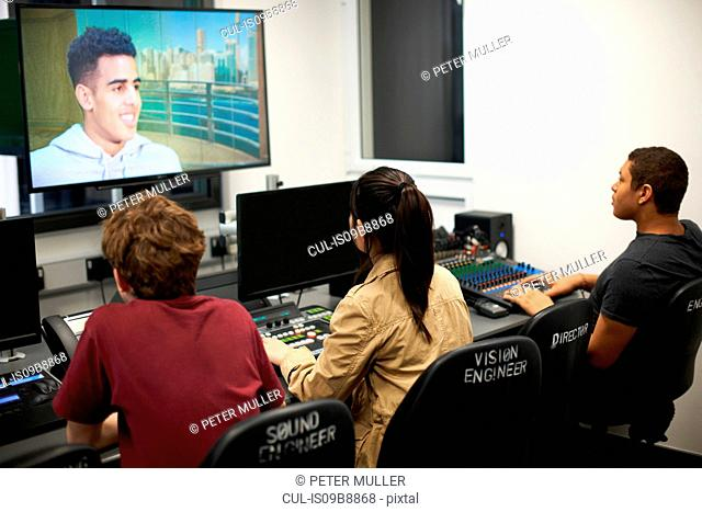 Young male and female college students at mixing desk watching TV screen