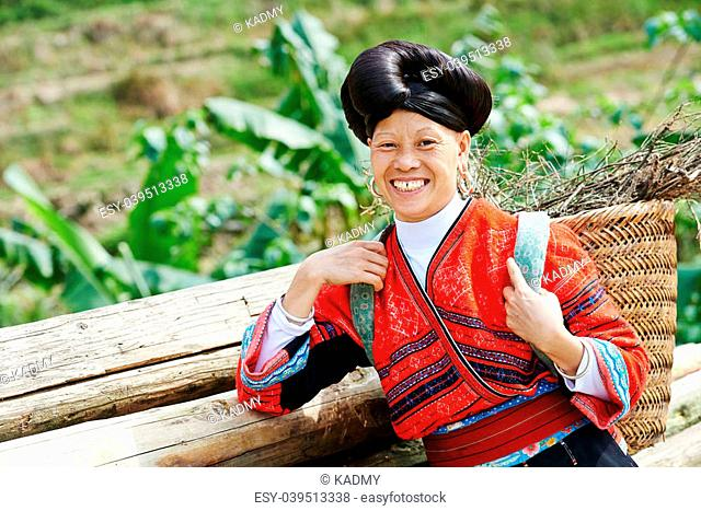 happy chinese minority woman Yao in traditional dresses outdoors
