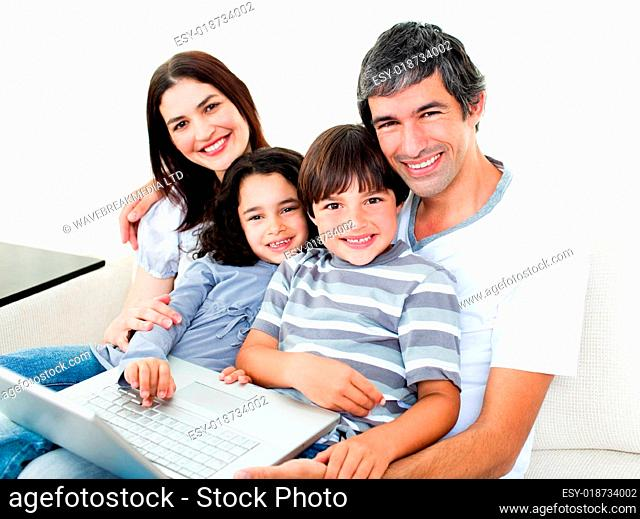 Happy family using a laptop sitting on sofa