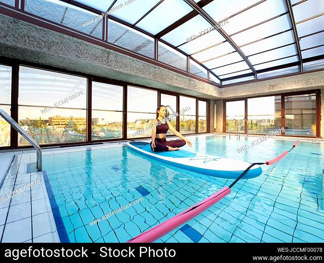 Female paddle yoga instructor meditating in lotus position over swimming pool