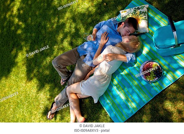 Young couple kissing on picnic blanket, overhead view