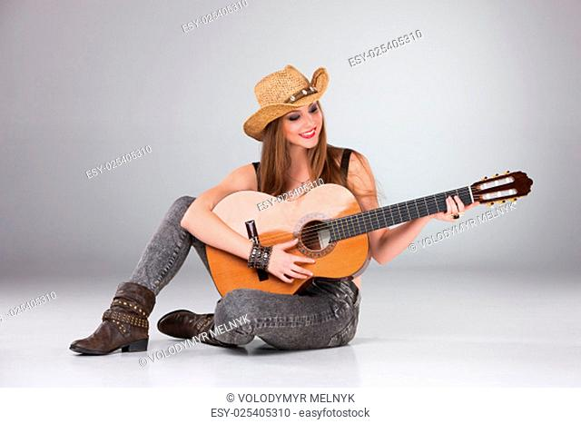 The beautiful girl in a cowboy's hat playing acoustic guitar on a gray background