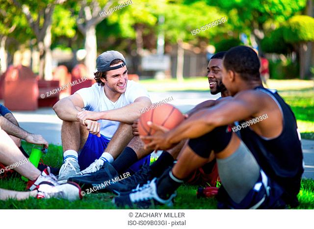 Group of male friends sitting together in park, laughing