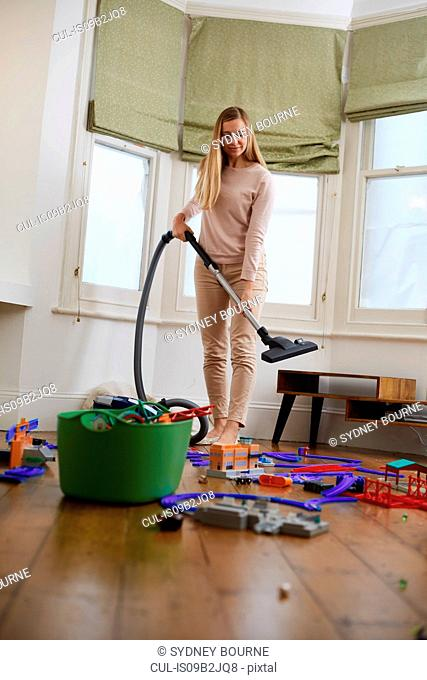 Mid adult woman with vacuum cleaner and scattered toys in living room