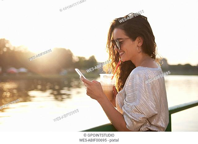 Smiling young woman with cell phone and takeaway drink at the riverside at sunset