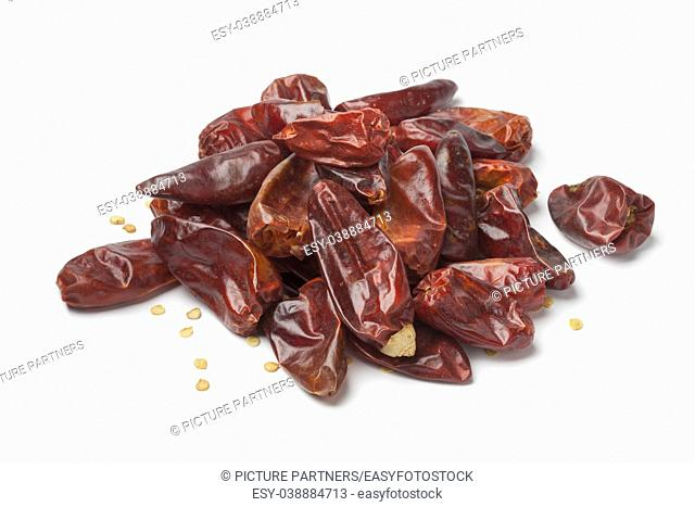 Heap of dried red hot chili peppers on white background