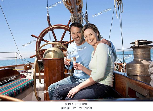 Caucasian couple toasting each other on sailboat