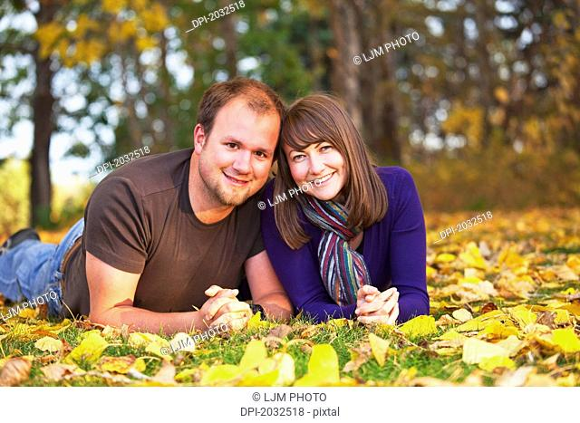 Portrait Of A Young Couple Laying In The Leaves In Autumn, Edmonton Alberta Canada