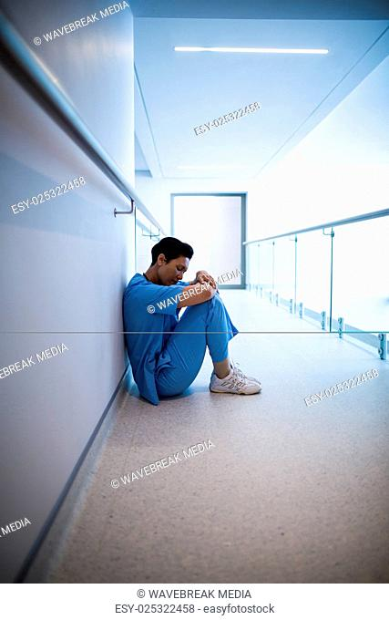 Tensed female nurse sitting in corridor