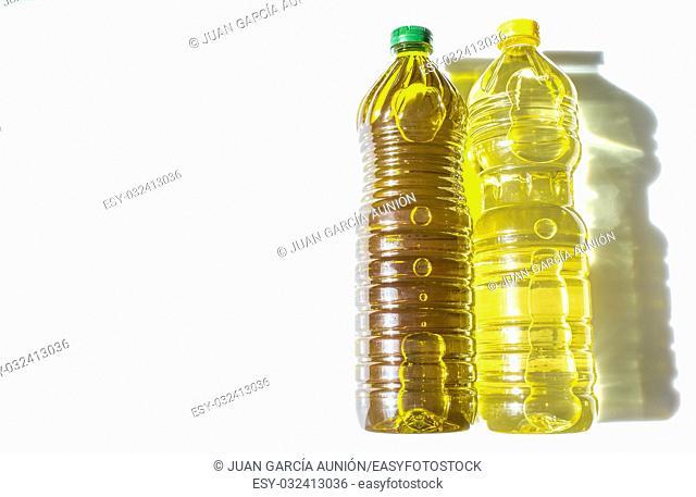 Olive versus sunflower oil bottled in PET. Isolated over white