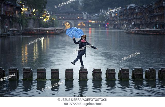 Happy girl in the ancient town, Fenghuang, Hunan Province, China