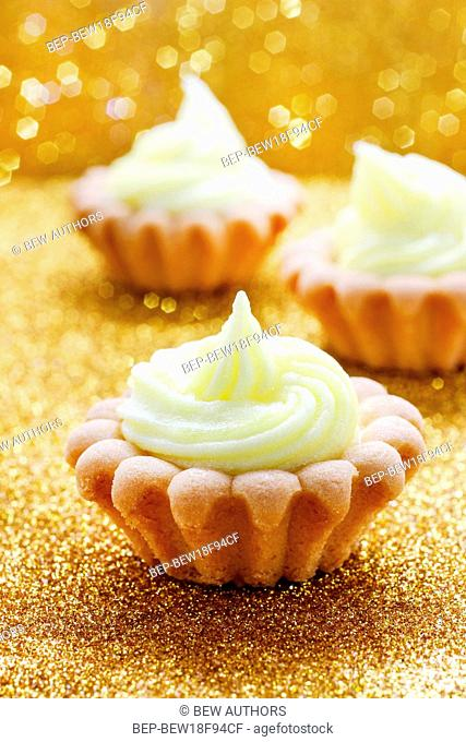 Tiny cupcakes on golden background. Party time