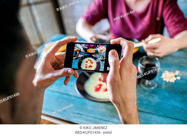 Man taking picture of of laid table with smartphone