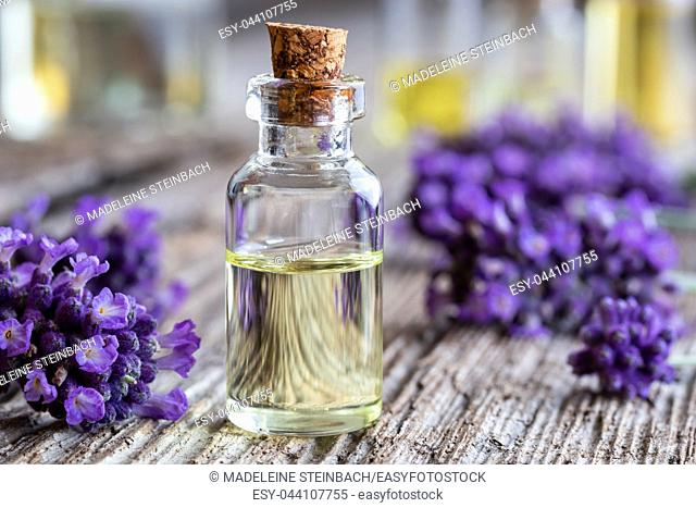 A bottle of essential oil with fresh lavender flowers on a rustic wooden background
