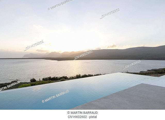 Tranquil sunset beyond infinity pool and ocean