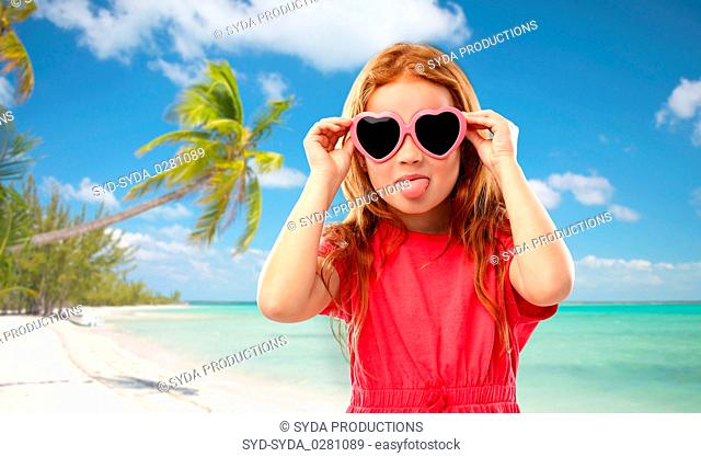 redhead girl in heart shaped sunglasses on beach