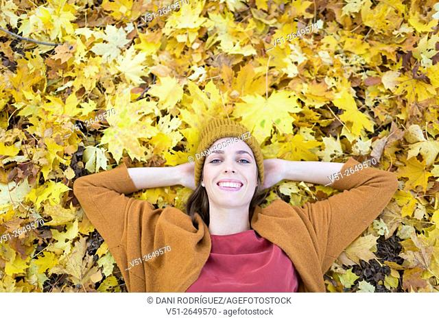 Brunette Woman in Park in Autumnn smiling at camera, view from above