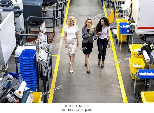 Three women with tablet walking and talking in factory shop floor