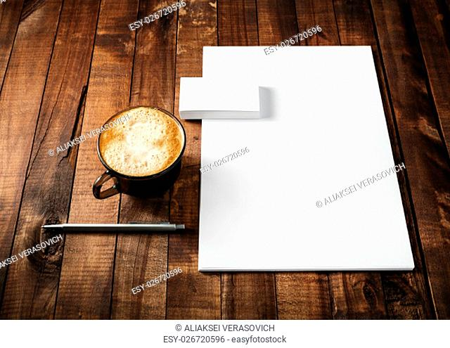 Blank paperwork and corporate identity template on vintage wooden table background. Blank letterhead, business cards, coffee cup and pen