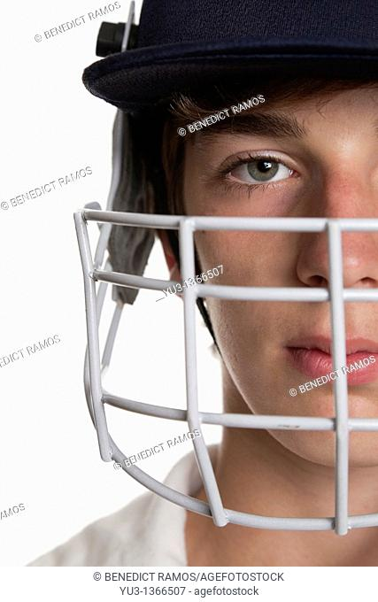 Portrait of teenage cricketer in protective helmet and visor