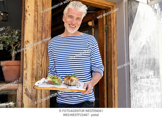 Mature man standing in front of his restaurant, serving a dish