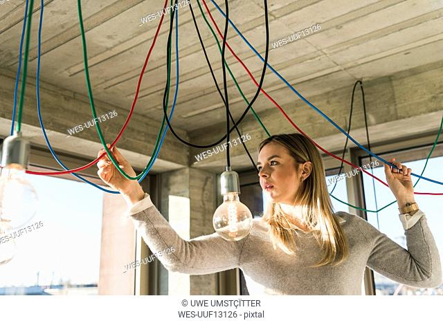 Young businesswoman in office examining cables at light bulbs