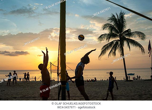 Phuket, Thailand, Asia - A group of locals plays volleyball in the sunset on Karon Beach