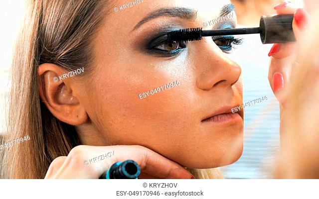 Portrait of young blonde woman posing while makeup artist painting her eyes with mascara