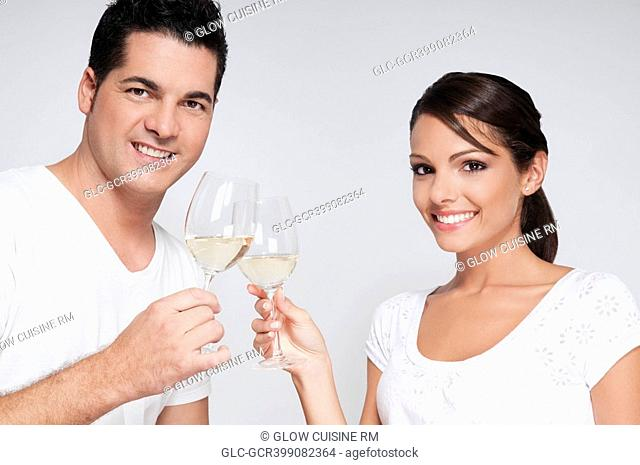 Couple toasting with white wine glasses