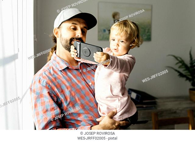 Father holding his little daughter on his arm, playing with his smartphone