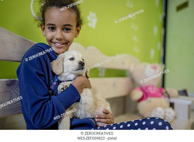 Girl holding labrador puppy at the veterinarian