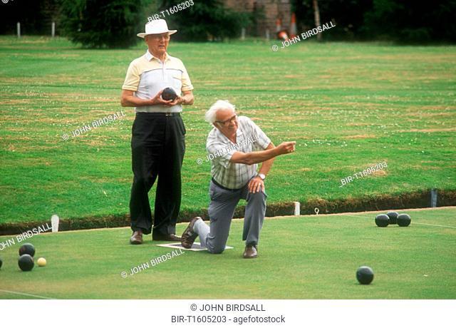 Elderly men bowling on green