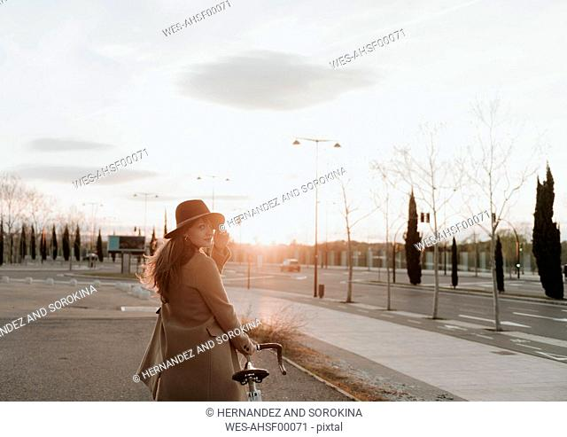 Young hipster woman going with a bicycle during sunset