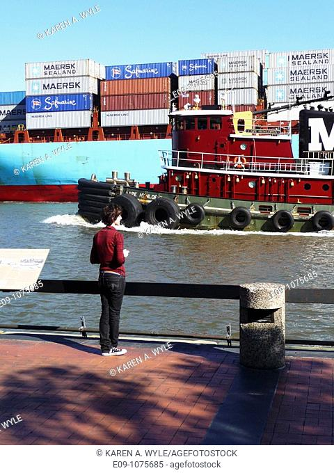 young woman with short hair, casual clothes, standing on riverfront walk at Savannah River, Savannah, Georgia, while tugboat and Maersk Line carrier ship pass...