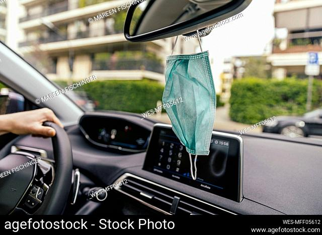 Protective mask hanging from rear-view mirror in car