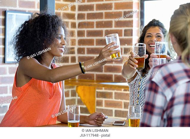Group Of Female Friends Making Toast In Bar Together