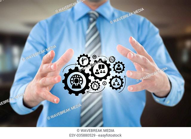 Business man interacting with people in cogs graphics against office background