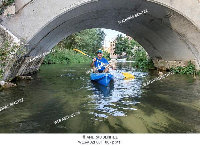 Spain, Segovia, Man in a canoe under a bridge