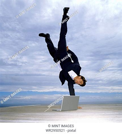 A man in suit doing a one armed handstand on a deck by the ocean, a laptop by his side