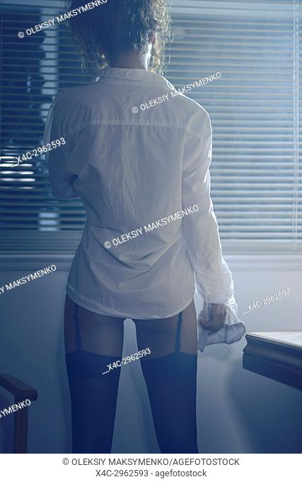 Back of a sexy woman wearing a white men's dress shirt and black stockings looking out of the window at night