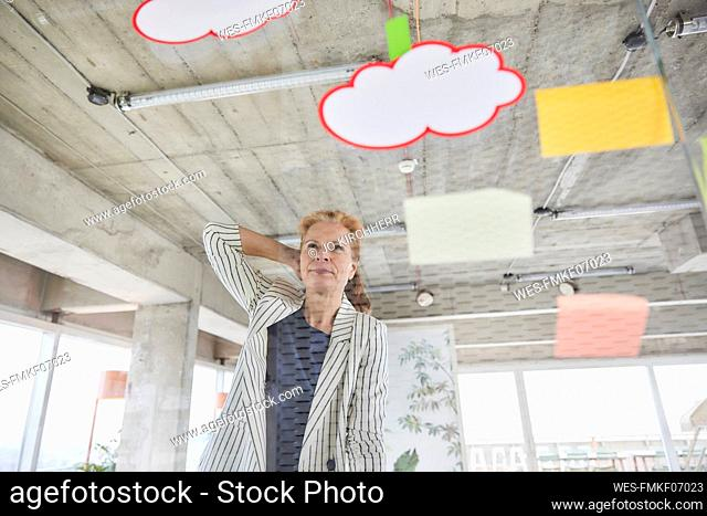 Female freelance worker with hand behind head seen through glass wall while looking at adhesive notes in office