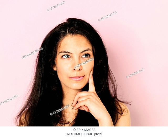 Portrait of young woman with black hair in front of pink background
