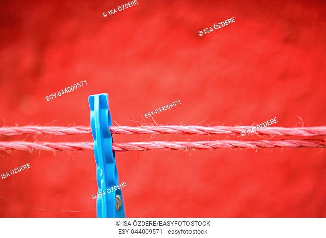 Vintage view of Blue Clothes peg pinned to a bench with red wall in a background hanging on a clothes rack