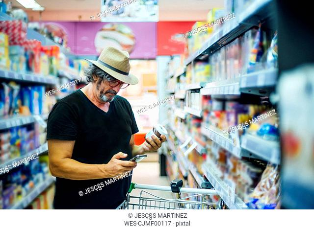 Senior man shopping in a supermarket using his smartphone