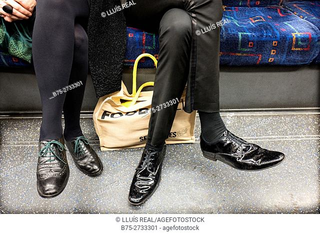 Man and woman's legs. Couple in London Underground, seated