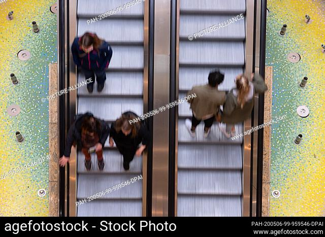 06 May 2020, Saxony, Dresden: Visitors to the Altmarkt-Galerie shopping centre stand on an escalator. In the Free State, shopping centres have been allowed to...